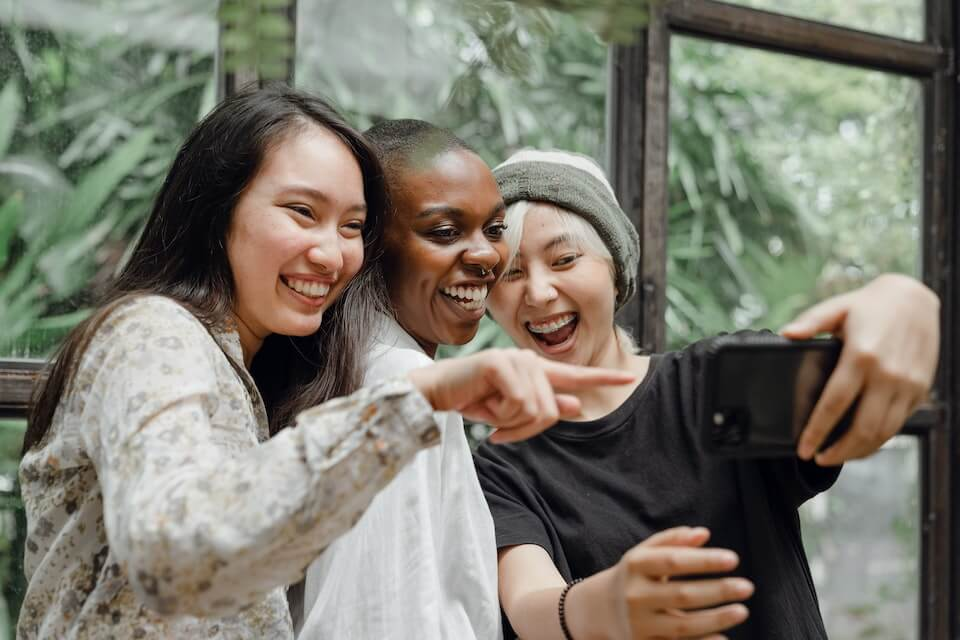 group of women taking picture to upload on social media